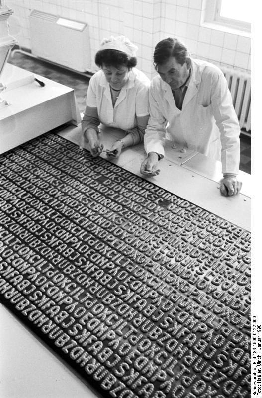 ADN-ZB/Häßler 22.1.90 Dresden: Russisch-Brot Zwar etwas kompliziert zu lesen, dafür umso schmackhafter ist der Text auf dem endlosen Stahl-Backblech der Russisch-Brot-Linie im VEB Dauerbackwaren Dresden. Im Dezember 1989 wurde hier eine Versuchsanlage in Betrieb genommen, die es ermöglicht, jetzt 600 statt bisher 260 Tonnen der Knabberei pro Jahr zu liefern. In 6,5 Minuten durchläuft das süße Kauderwelsch den Backprozeß. Produktionsstättenleiter Manfred Keese und TKO-Leiterin Renate Keese testen die Backqualität. Trotz der Produktionsteigerung in Dresden wird man Russisch-Brot künftig noch oft vergeblich in den Kaufhallenregalen suchen. Der Dresdner Betrieb